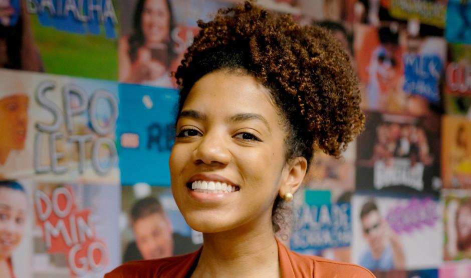 Nathália Cruz- mulher negra de cabelo cacheado, usando camiseta marrom- sorrindo
