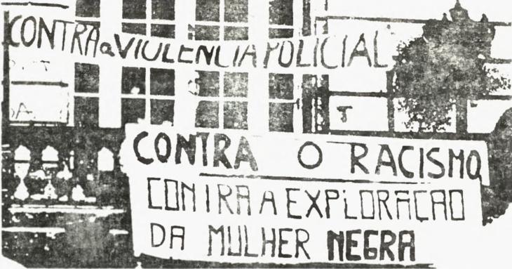 Foto em preto e branco de cartazes contra o racismo e a violência policial
