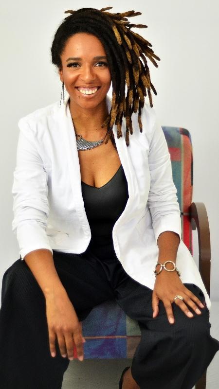 Camila de Moraes - mulher negra, com dreads, usando macacão preto e blazer branco- sentada em uma cadeira sorrindo