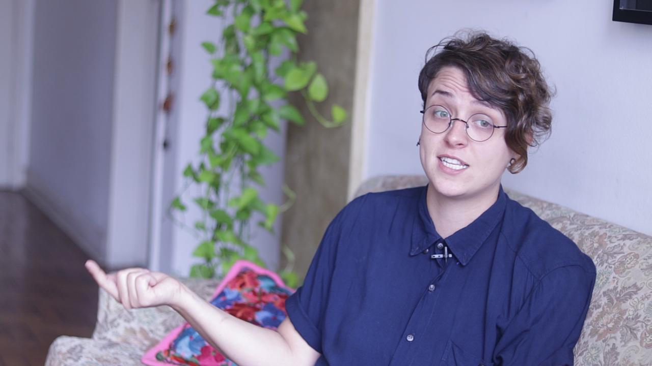 Debora Baldin- mulher branca de cabelo curto, usando óculos e camiseta azul marinho- sentada em um sofá