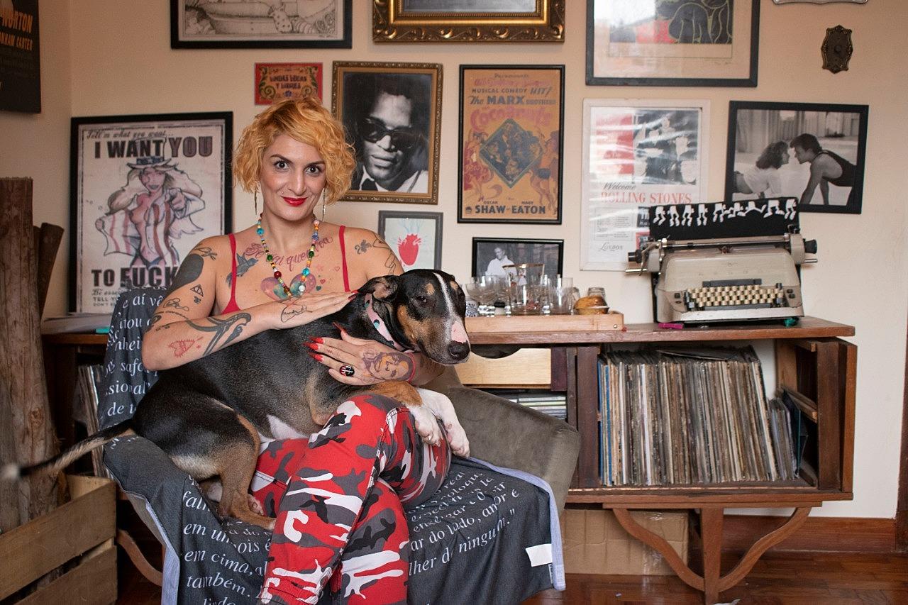 Clara Averbuck - mulher branca de cabelo loiro, usando mascação vermelho estampado- sentada em uma poltrona e segurando um cachorro no colo