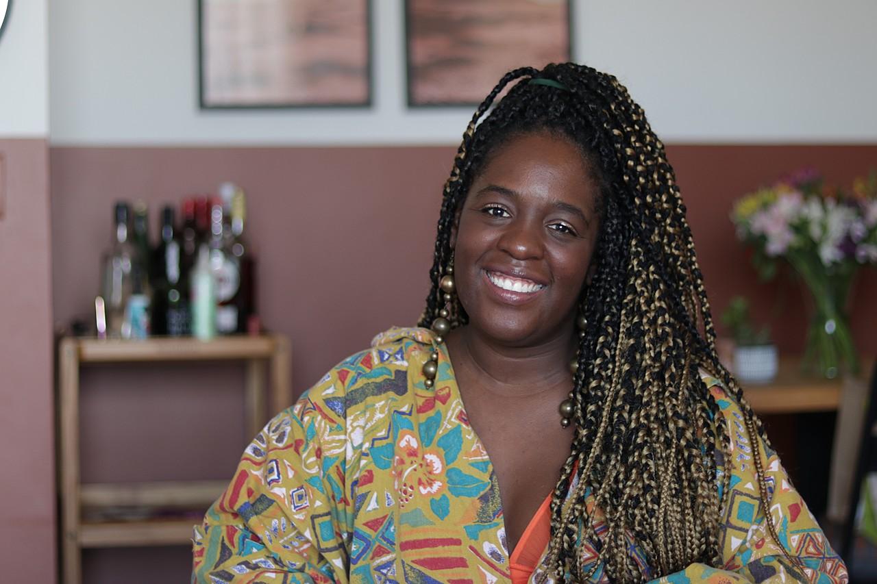 Ana Paula Xongani - mulher negra, usando tranças e camiseta com estampa colorida- sentada sorrindo