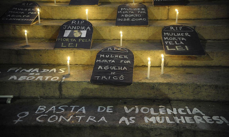 Imagem de uma escadaria com caixões de papelão e velas nas escada