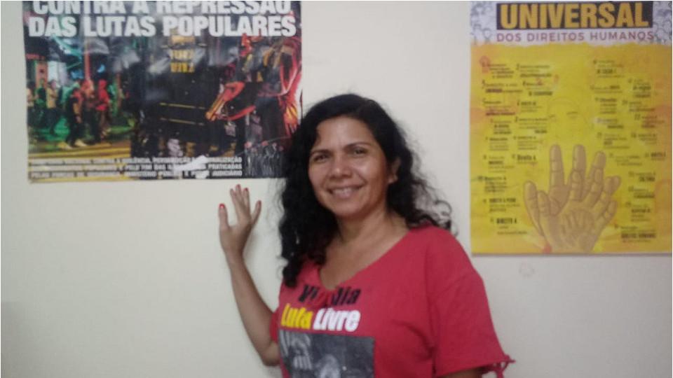 """Neila Gomes - mulher de cabelo cacheado, usando camiseta vermelha escrito """"Lula Livre''- em pé apoiada na parede"""