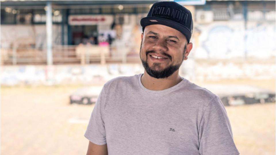 Max Maciel - homem negro de pouca barba, usando boné preto e camiseta cinza- em pé sorrindo