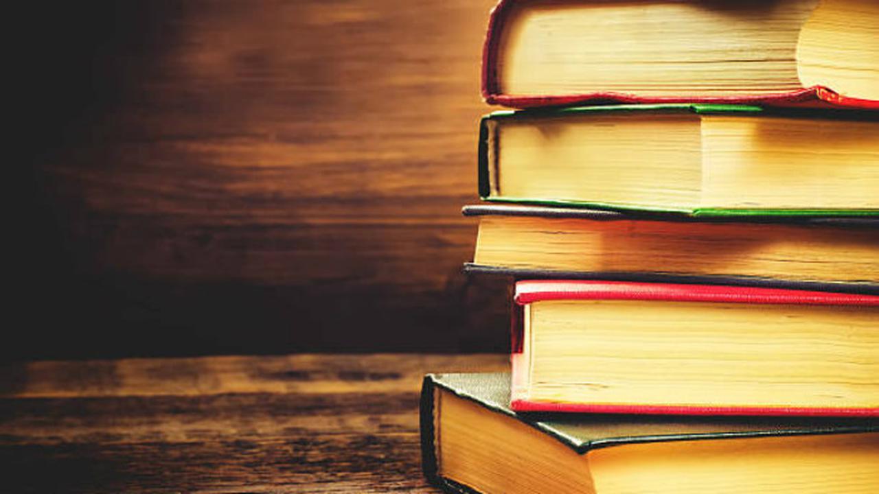 Imagens de livros em uma mesa de madeira