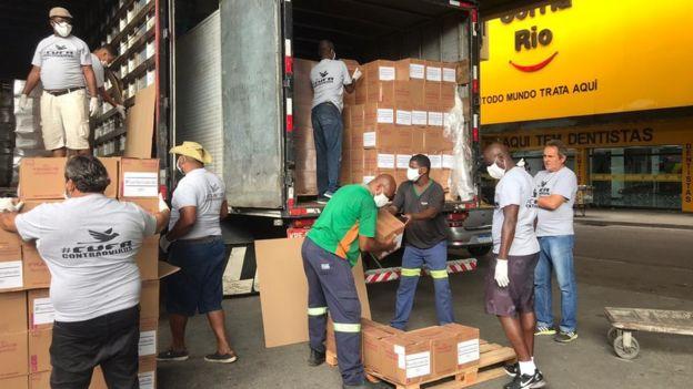 Foto de dois caminhões cheio de caixas sendo descarregados