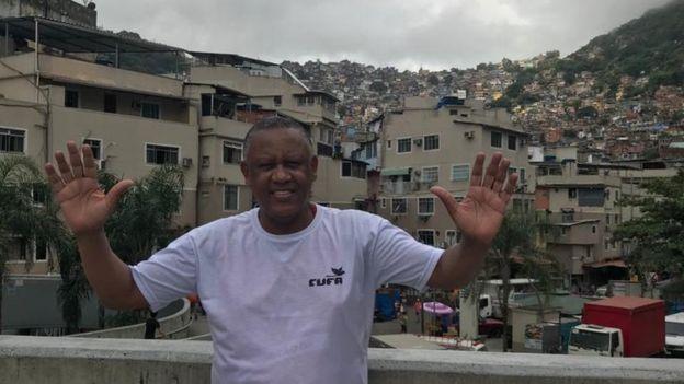 Celso Athayde - homem negro de pouco cabelo, vestindo camiseta branca- em pé sorrindo e acenando com as duas mãos