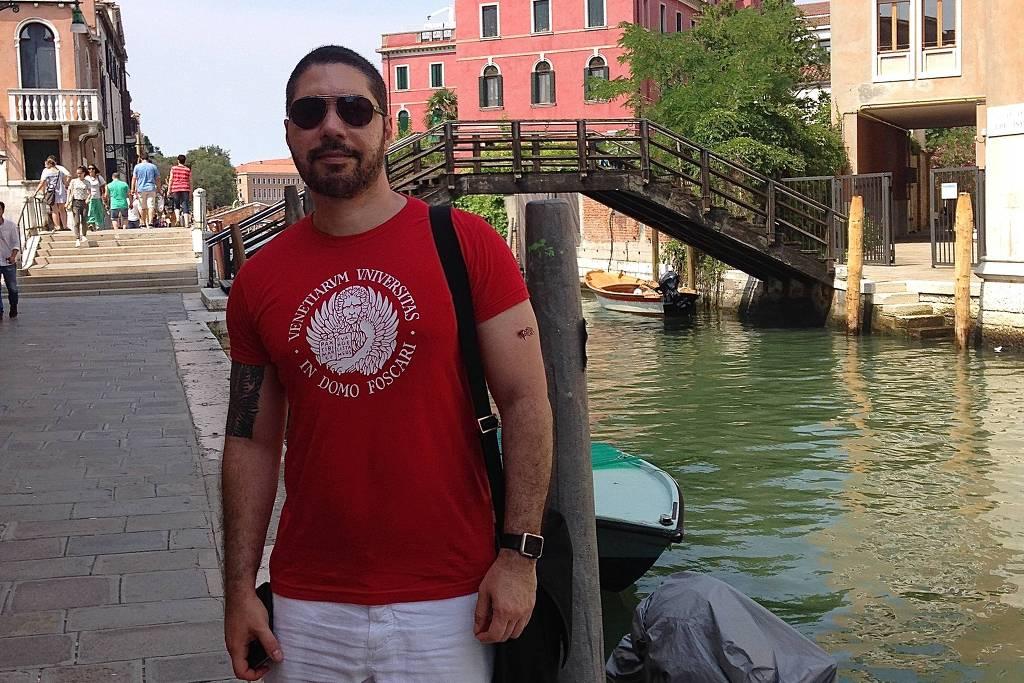 Alexey Dodsworth- homem branco, de pouca barba e cabelo, vestindo camiseta vermelha e bermuda branca e usando óculos de grau- em pé fazendo pose ao lado de um rio