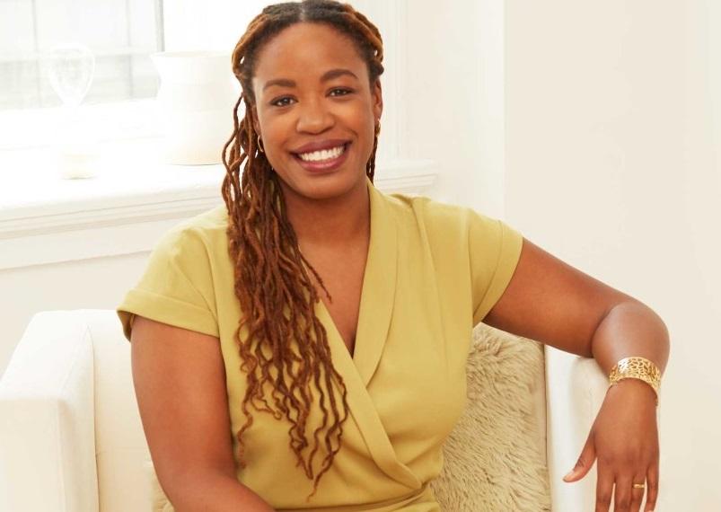 Heather C. McGhee- mulher negra, de tranças, vestindo vestido beje- sorrindo, sentada em uma poltrona