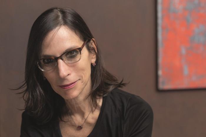 Lilia Schwarcz- mulher branca, de cabelo liso que vai até a altura do ombro, usando óculos de grau e camiseta preta- sentada olhado para frente