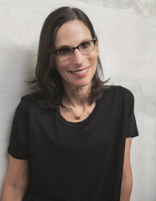 Lilia Schwarcz- mulher branca, de cabelo liso que vai até a altura do ombro, usando óculos de grau e camiseta preta- em pé sorrindo