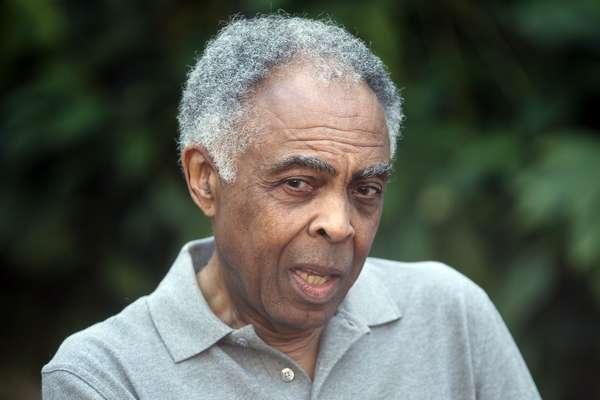 Foto de Gilberto Gil- homem idoso negro, de cabelo grisalho, vestindo camiseta cinza- sentado olhando para o lado