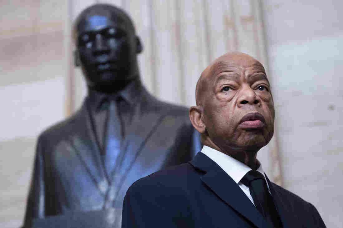 John Lewis- homem idoso nefro, careca, usando terno e gravata- em pé ao lado de uma estatua