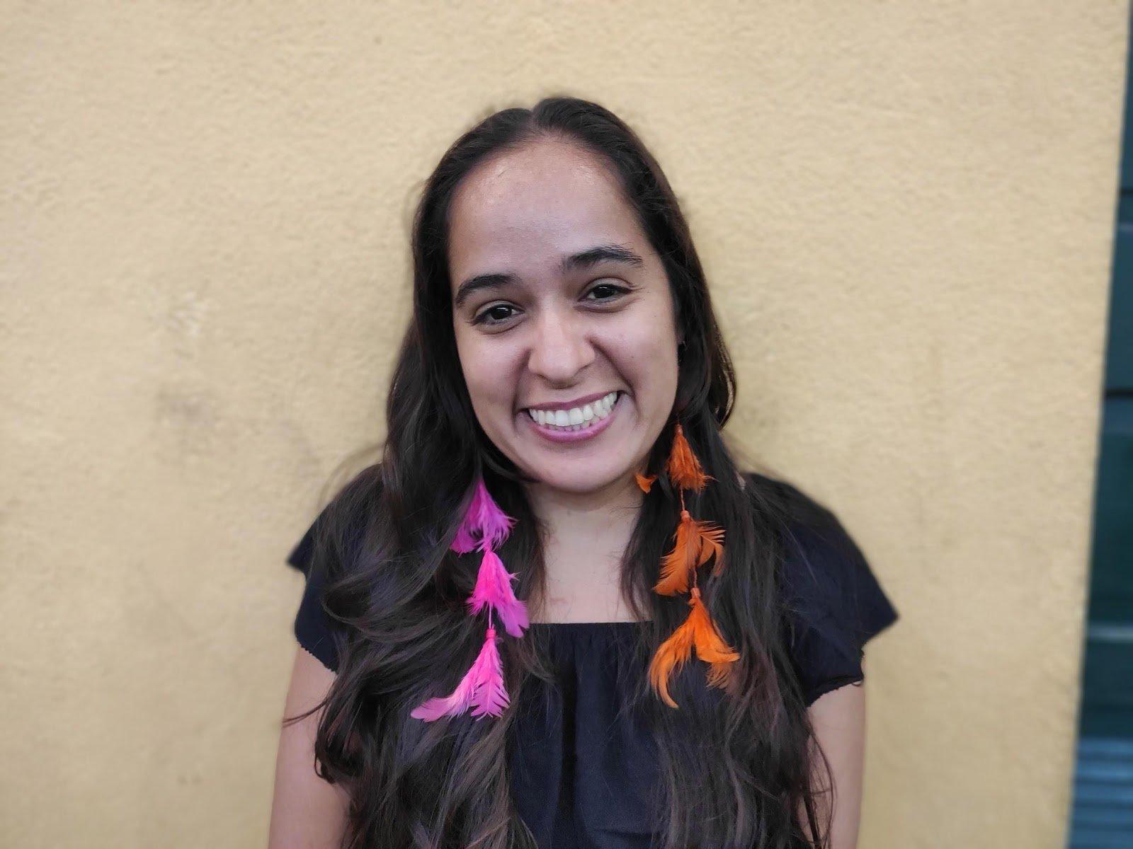 Geni Núñes,- mulher, de cabelo ondulado e longo, usando brinco de penas e camiseta preta- em pé sorrindo