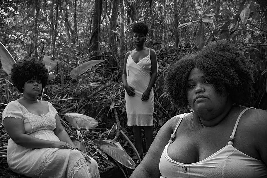 Foto em preto e branco de três mulheres negras de cabelo crespo, sentadas em meio a mata