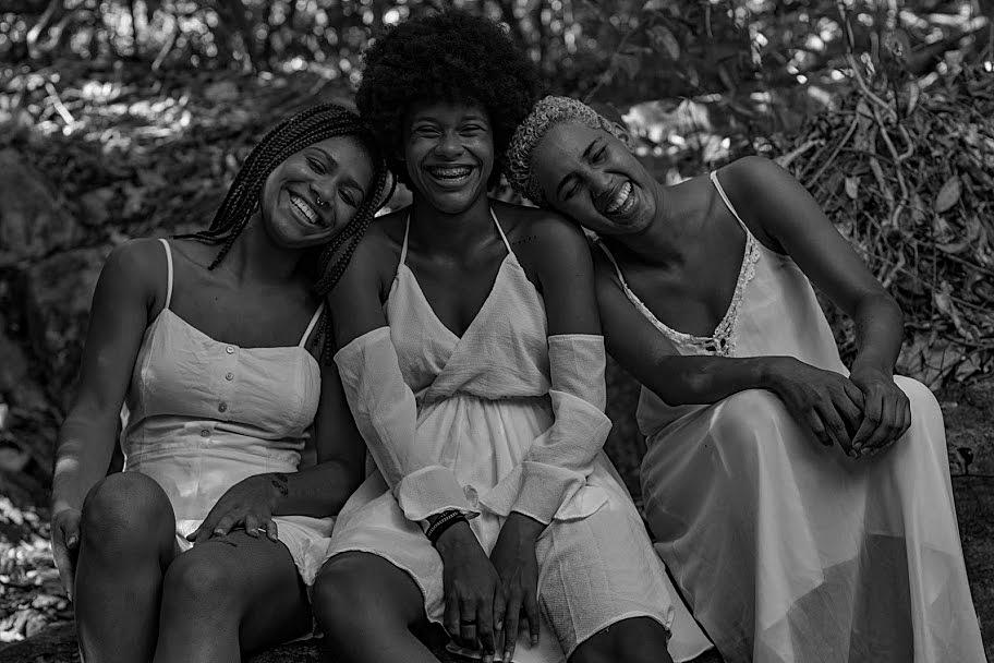 Foto em preto e branco de três mulheres negras com cabelos distintos- a primeira usa tranças, a segunda black e a terceira tem o cabelo bem curto - sentadas sorrindo