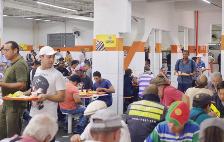 Mesas cheias de pessoas almoçando