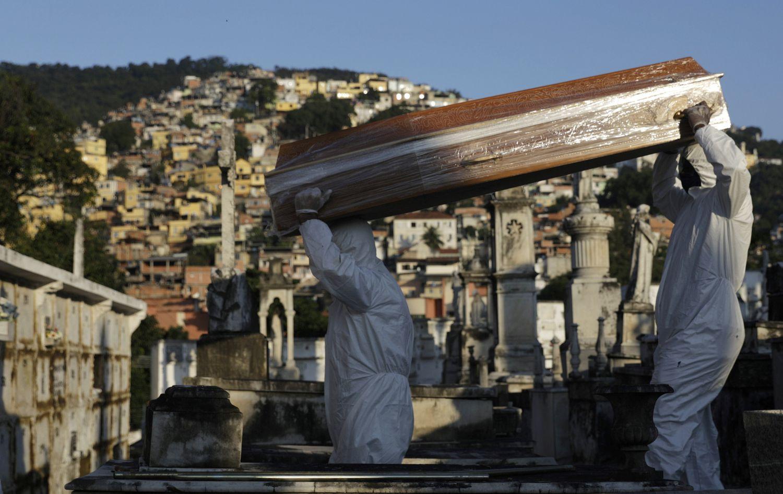 Coveiros carregam o caixão de Antonia Rodrigues, vítima do coronavírus no Rio.(FOTO: RICARDO MORAES / REUTERS)