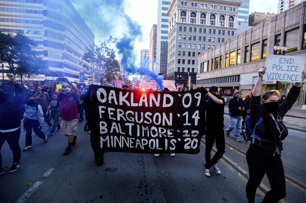 Em Oakland, manifestantes pela morte de George Floyd seguram cartaz com datas e cidades em que homens negros foram mortos por policiais brancos: Oakland, em 2009; Ferguson, em 2014; Baltimore, em 2015; e Minneapolis, 2020. (Foto: Noah Berger/AP)