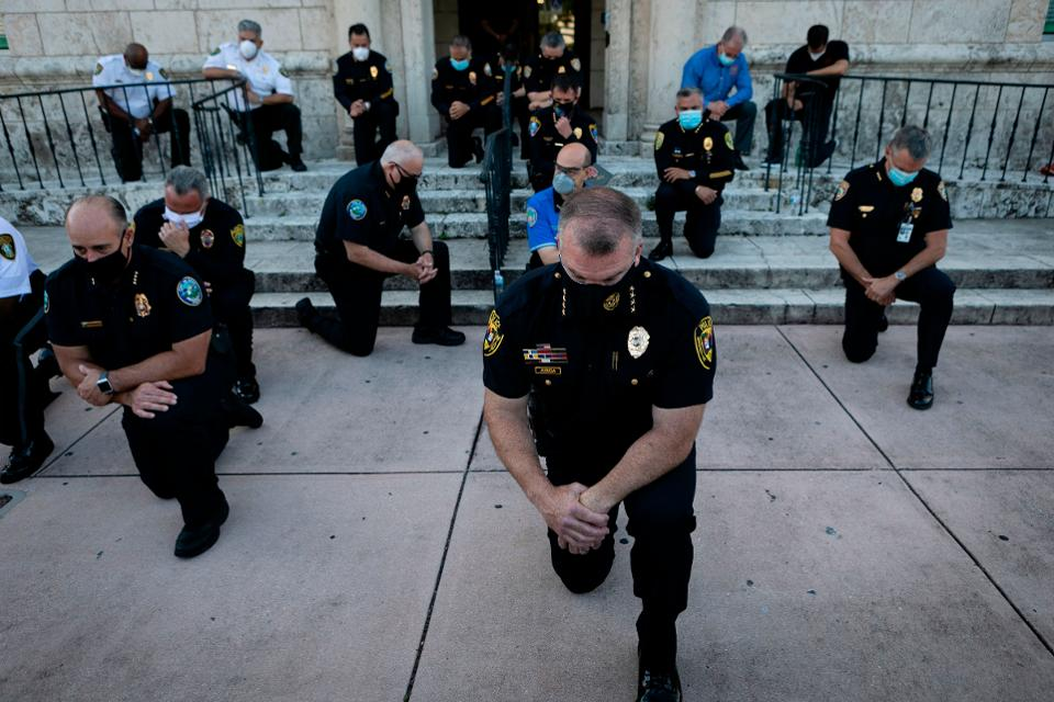 Police officers kneel during a rally in Coral Gables, Florida, on Saturday in response to the death ... [+] EVA MARIE UZCATEGUI/AFP VIA GETTY IMAGES