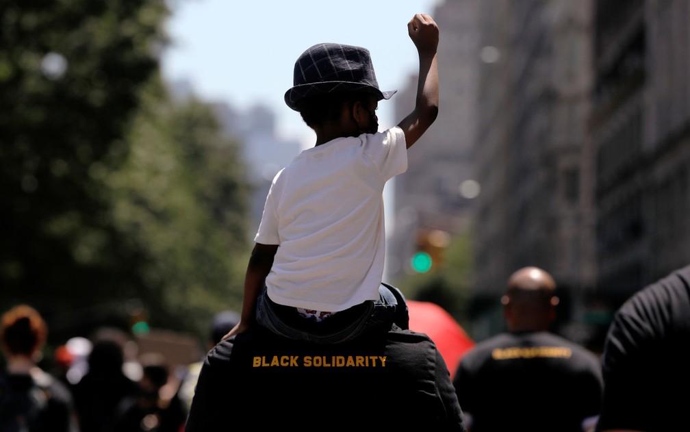 Criança participa de marcha no Central Park West em celebração ao Juneteenth em Nova York, na sexta-feira (19) (Foto: Reuters/Andrew Kelly)