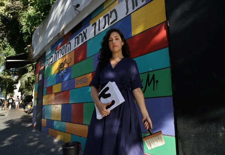 """Ilana Weizman, uma das criadoras do """"HaStickeriot"""", que prega cartazes nas ruas, em Tel Aviv, Israel (Foto: AFP)"""