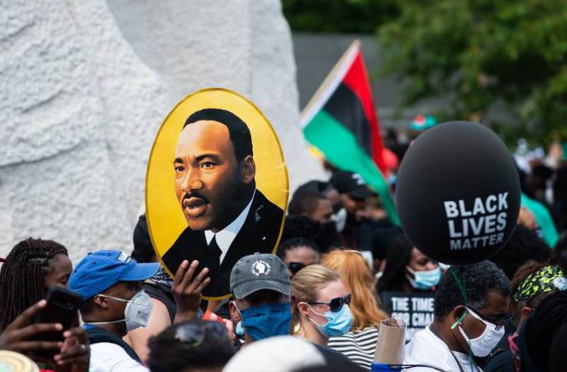 """Manifestante com uma imagem de Martin Luther King durante uma reedição da marcha que, há 57 anos, resultou no histórico discurso """"Eu tenho um sonho"""" (Foto: Roberto Schmid/ AFP)"""