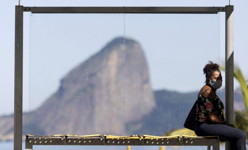 Mulher com máscara de proteção sentada em ponto de ônibus em Niterói, com o Pão de Açúcar no fundo.RICARDO MORAES / REUTERS