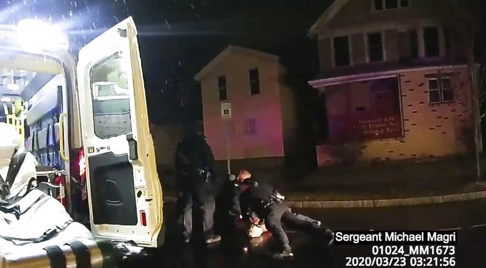 Policiais ainda seguram Daniel Prude, um homem negro, no chão mesmo com a presença de uma ambulância — Foto: Rochester Police via Roth and Roth LLP via AP