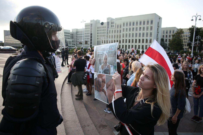 Uma mulher segura uma foto em frente a um policial de uma pessoa torturada durante protesto em Minsk neste sábado.(Foto: TUT.BY / REUTERS)