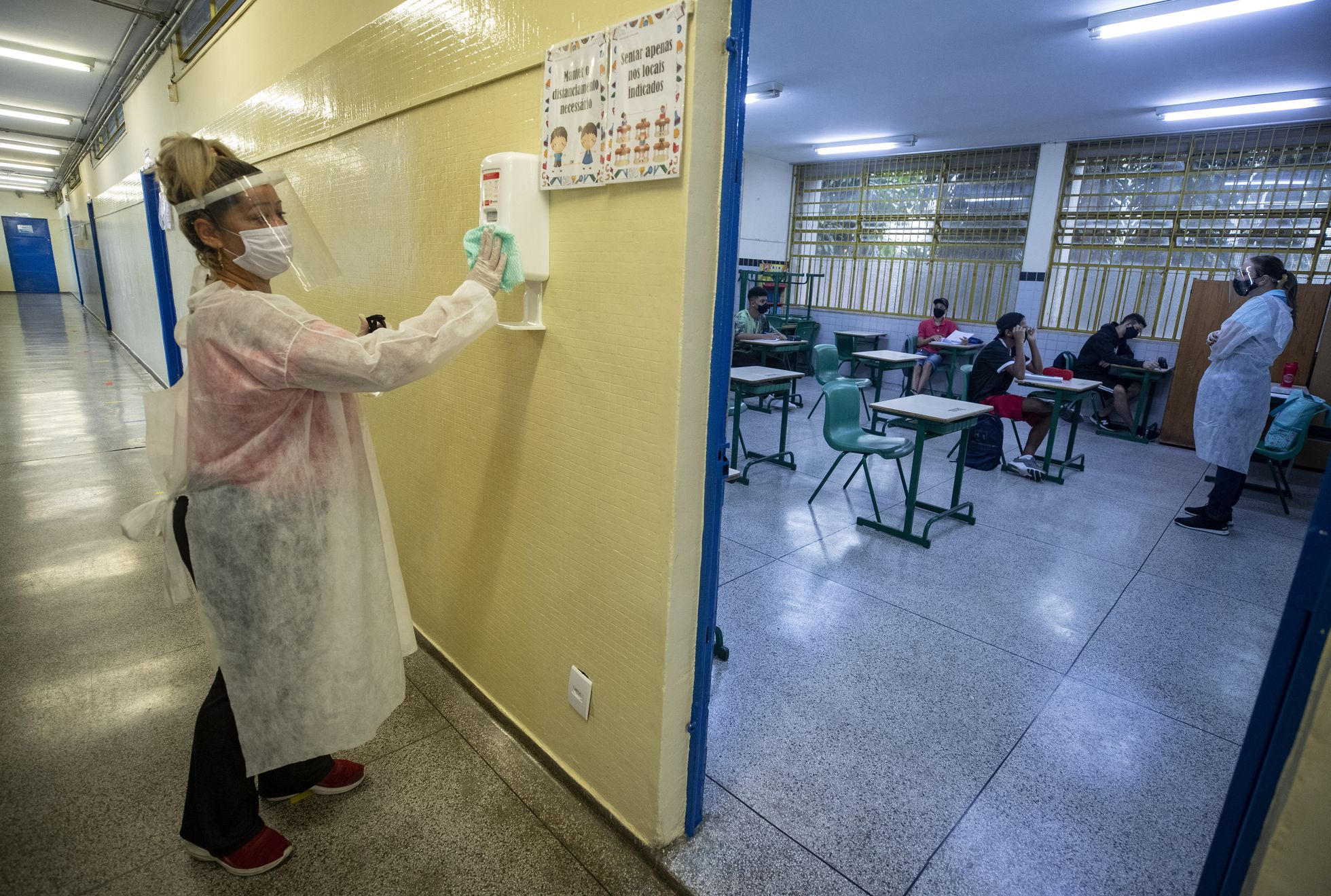 Mãe de aluno, contratada em um programa de temporários da Prefeitura, desinfeta um recipiente de álcool gel na escola de ensino fundamental Sylvia Martin Pires em São Paulo, em 8 de março de 2021. (Foto: ANDRE PENNER / AP)