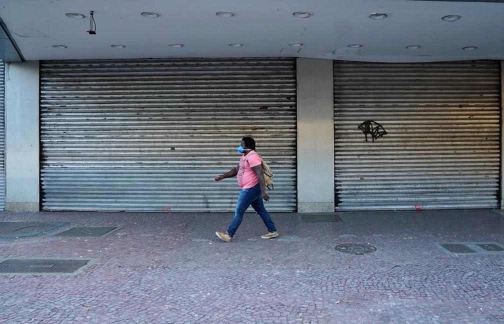 Foto registrada em 25 de março de 2020 mostra mulher caminhando no centro de Madureira, na Zona Norte do Rio, com comércio fechado — Foto: Marcos Serra Lima/G1