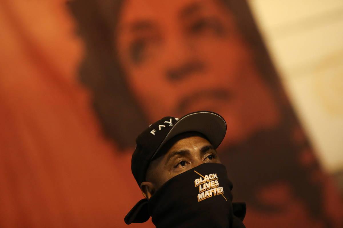 Diante de pôster de Marielle, manifestante participa de protesto contra violência policial e racismo no Rio - Ricardo Moraes/Reuters
