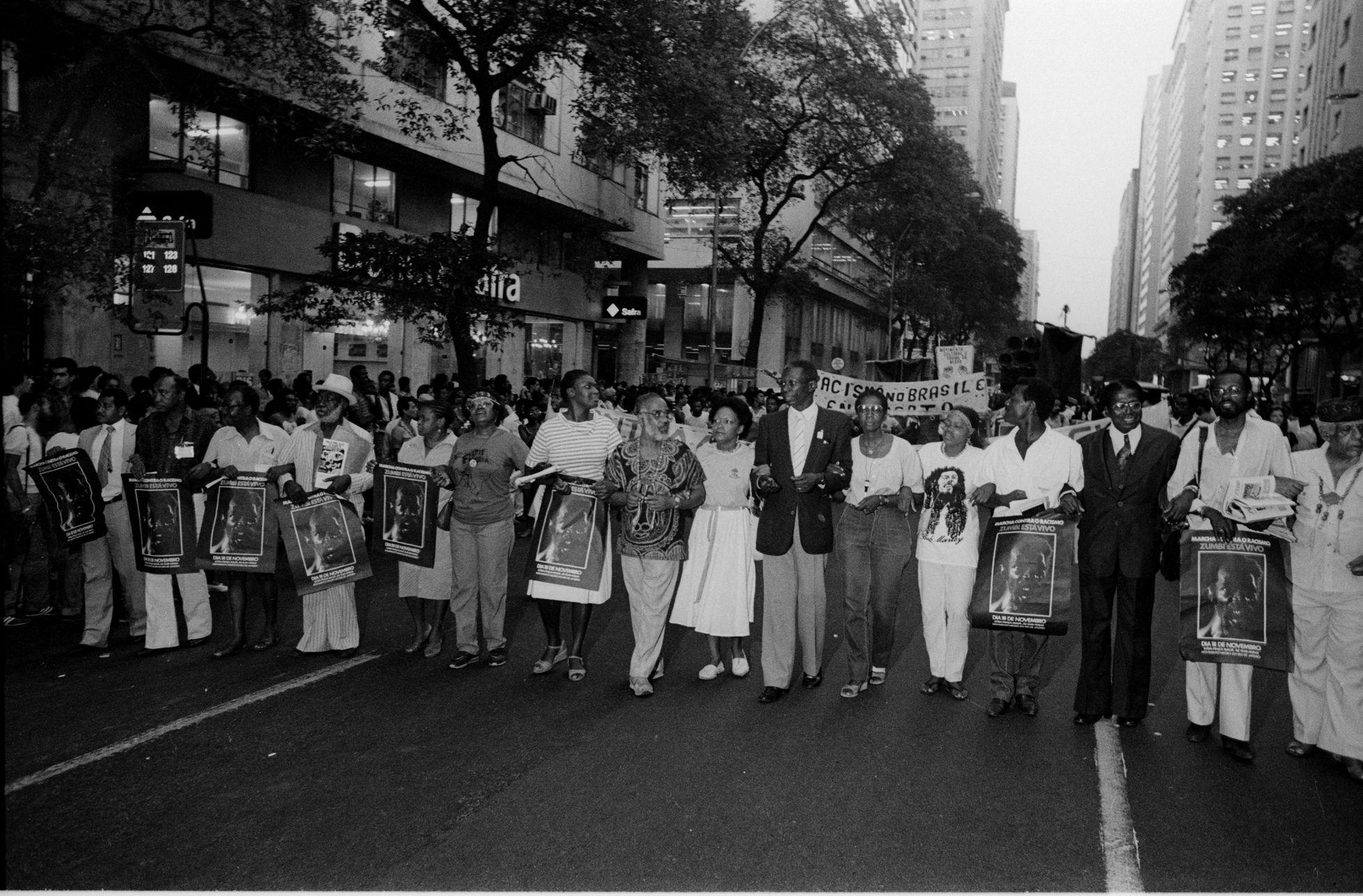 """Ativistas como Lélia Gonzalez, Benedita da Silva e Abdias Nascimento na marcha """"Zumbi está vivo"""", realizada no Rio de Janeiro em 1983. Foto faz parte do acervo de Januário Garcia que está sendo preservado.JANUÁRIO GARCIA"""